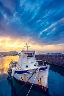 Stara łódź rybacka w porcie naousa na zachód słońca. paros lsland, grecja