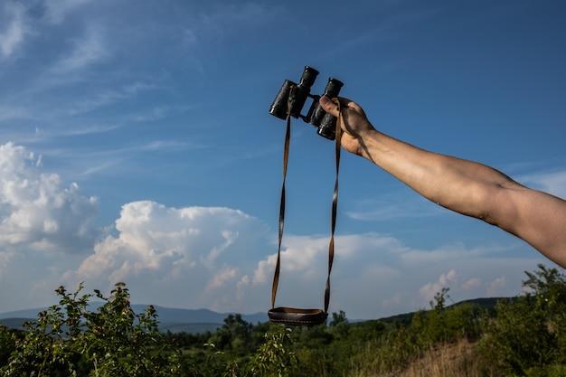 Stara lornetka w ręku mężczyzna trzyma lornetkę w dłoniach na tle pochmurnego nieba