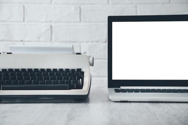 Stara maszyna do pisania i laptop na biurku