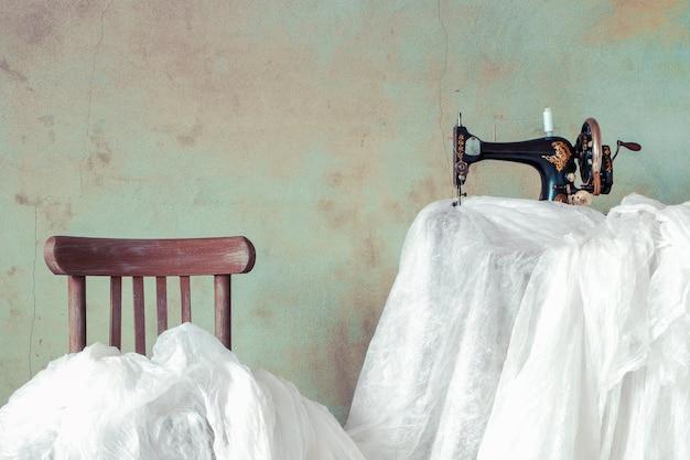Stara maszyna do szycia i dużo białego materiału nad krzesłem i stołem