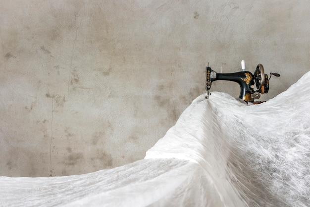 Stara maszyna do szycia i dużo białego materiału