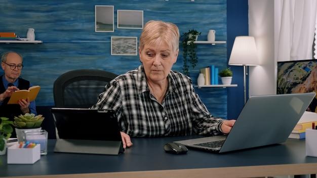 Stara menedżerka korzysta jednocześnie z laptopa i tabletu, pracując w domowym miejscu pracy dla start-upu firmy...
