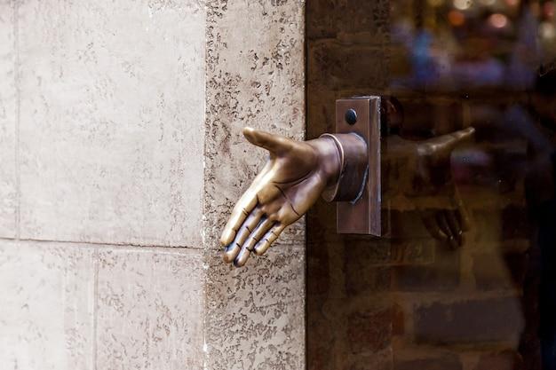 Stara metalowa klamka w kształcie dłoni na szklanych drzwiach we lwowie, ukraina