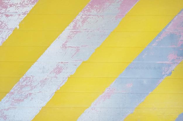 Stara metalowa powierzchnia z łuszczącą się farbą i ukośnymi paskami