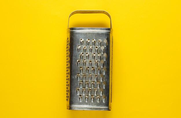 Stara metalowa tarka na żółtym papierze tabeli strzał studio
