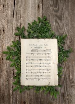 Stara muzyka sheetwooden tło gałąź choinki cicha noc kolęda stary papier 1900