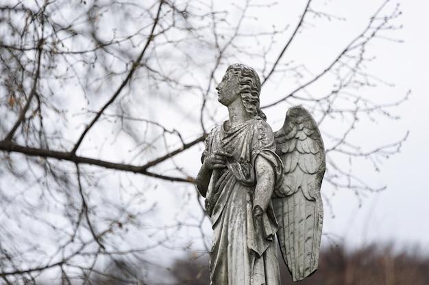 Stara nagrobkowa rzeźba anioła ze złamaną ręką i skrzydłami na cmentarzu
