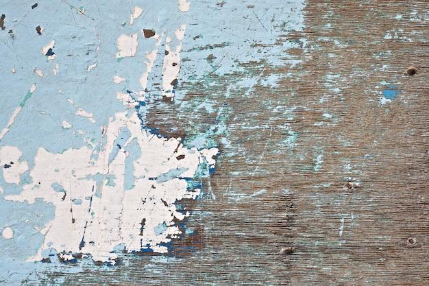 Stara niebieska pomalowana tekstura drewnianego krzesła z kawałkami piasku na wierzchu