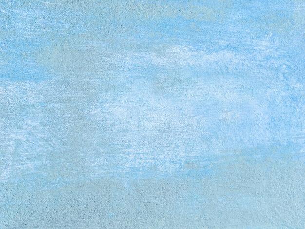 Stara niebieska ściana pokryta brudnym, nierównym tynkiem.