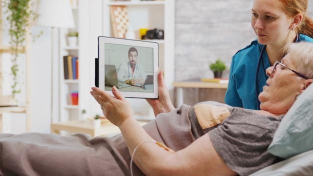 Stara niepełnosprawna kobieta leżąca w szpitalnym łóżku podczas wideorozmowy online z lekarzem. obok niej jest pielęgniarka