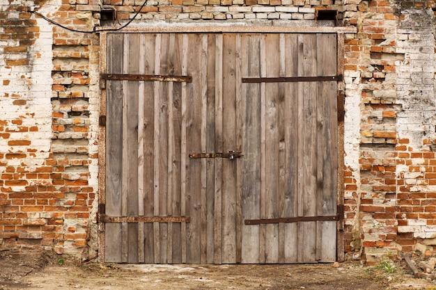 Stara obora. duża drewniana brama i suszone drewno. stary ceglany budynek