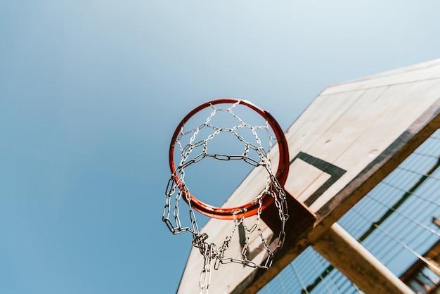 Stara obręcz do koszykówki na tle błękitnego nieba