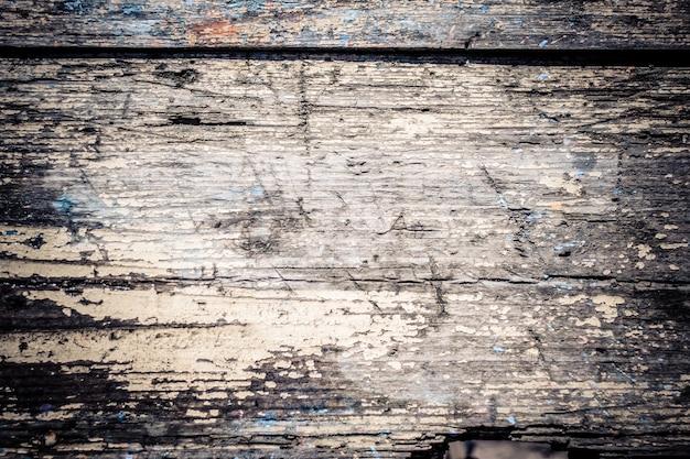 Stara odrapana drewniana powierzchnia z bliska z pękniętą farbą