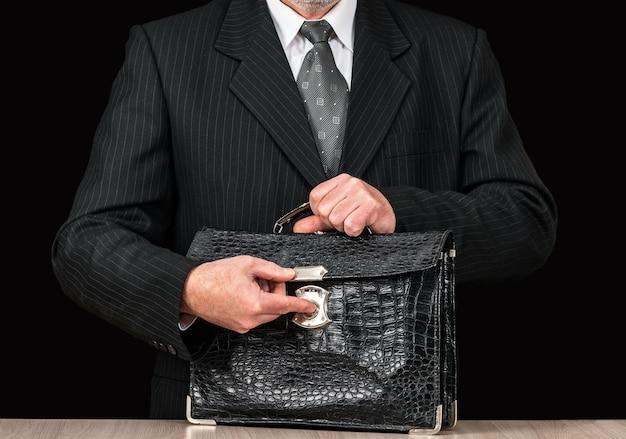 Stara odrapana skórzana teczka w dłoni biznesmena