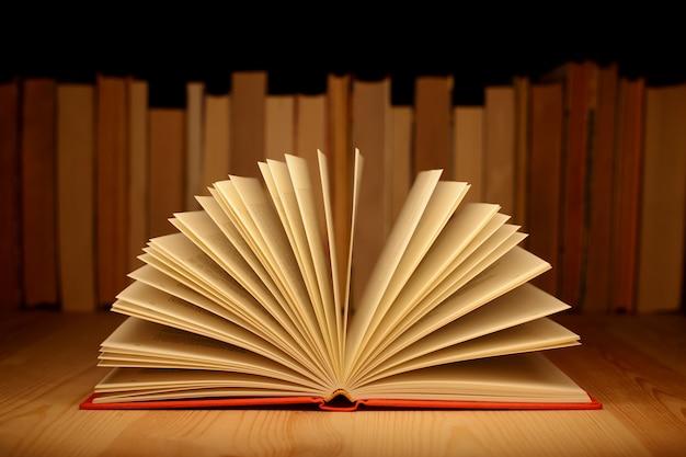 Stara otwarta książka na drewnianym stole blisko rzędu wiele stare i nowe książki. pojęcie wiedzy, informacji.