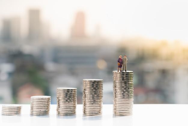 Stara para stoi na szczycie stosu monet.