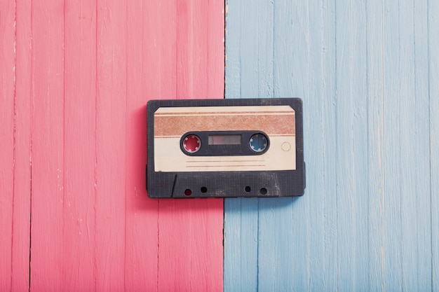 Stara plastikowa kaseta na różowo-niebieską drewnianą. koncepcja muzyki retro