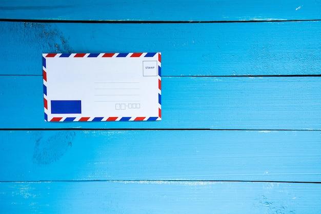 Stara poczta koperta na błękita stołu drewnie