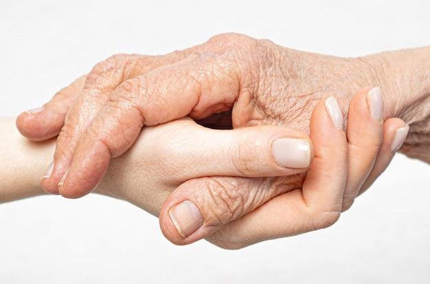 Stara pomarszczona dłoń leży na zbliżeniu młodej dłoni