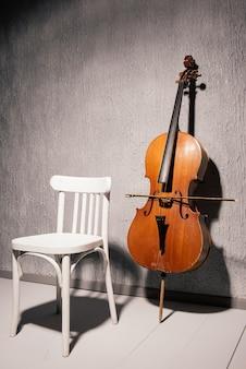 Stara poobijana wiolonczela i krzesło stojące w pobliżu szarej ściany w szkole lub pokoju do ćwiczeń.