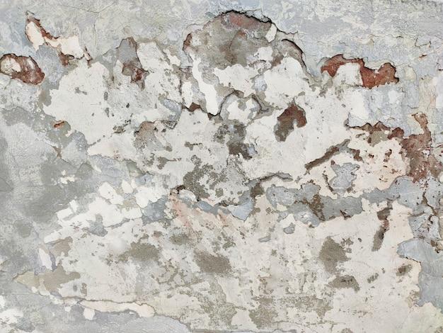 Stara popękana ściana jest beżowo-szara. tło mody grunge.