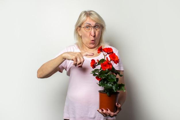 Stara przyjazna kobieta w swobodnej koszulce i okularach trzyma kwiatka pokoju i wskazuje palcem z zaskoczoną twarzą na odosobnionej lekkiej ścianie. twarz emocjonalna. pojęcie pielęgnacji roślin, ogród przydomowy