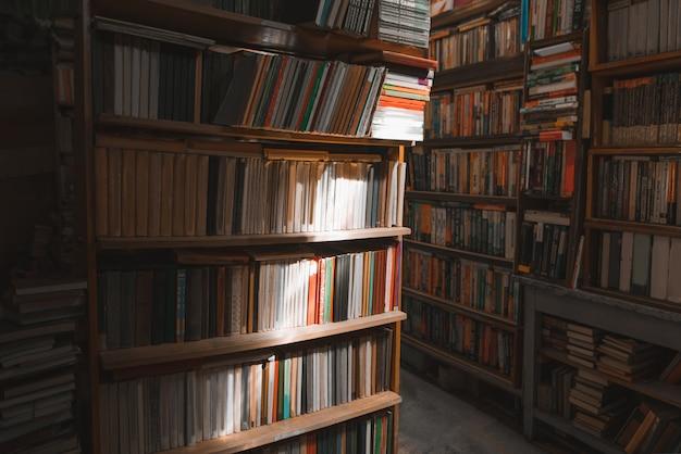 Stara przytulna biblioteka. gra światła i cienia na półkach z książkami w bibliotece.