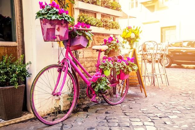Stara przytulna ulica w trastevere, rzym, włochy z fioletowym rowerem.