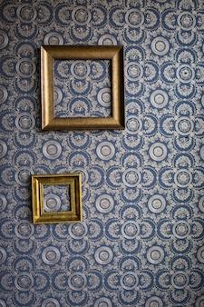 Stara rama wykonana z gipsu, na niebieskiej tapecie