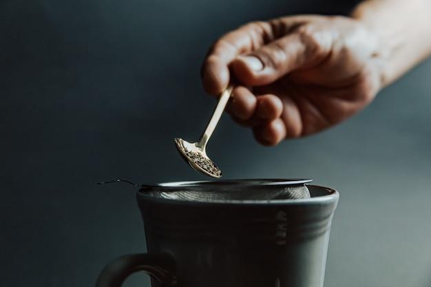 Stara ręka przygotowująca herbatę na ciemnym tle i ciemnych barwach