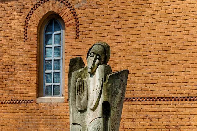 Stara religijna statua płaczącej kobiety na tle ceglanej fasady budynku o
