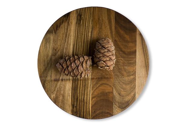 Stara rozdrobniona drewniana deska do krojenia z szyszek cedrowych, na białym tle na białej powierzchni. zbliżenie teksturowane, widok z góry.