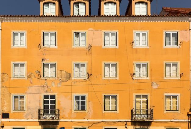 Stara ściana budynku z oknami i balkonami