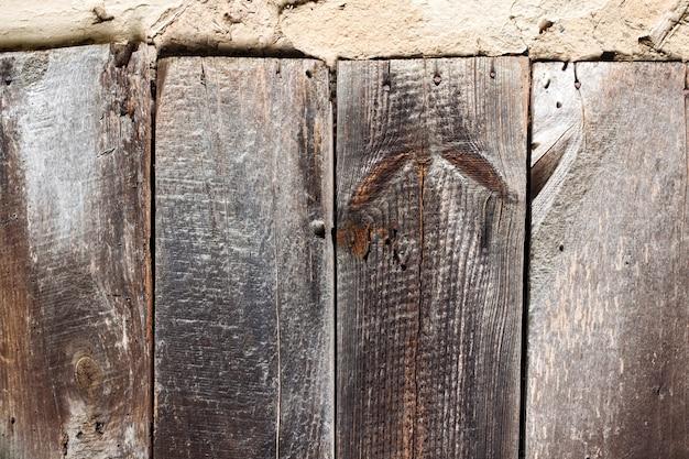 Stara ściana kolby z popękaną powierzchnią i starymi drewnianymi deskami