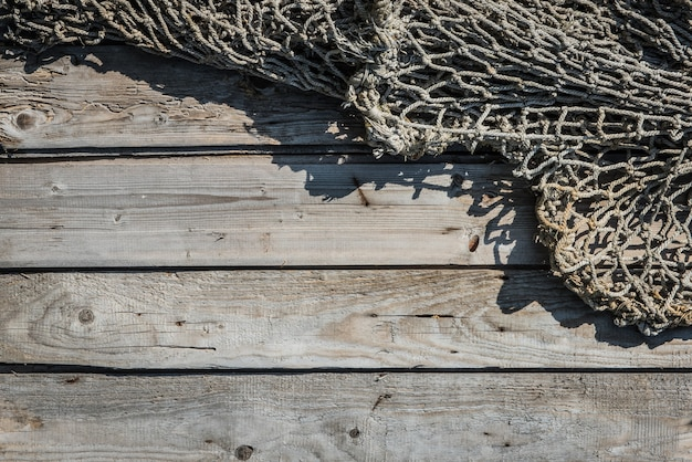 Stara sieć rybacka na drewnianej ścianie, tekstura sieci rybackiej ludu rybaka, tkana nylonową liną