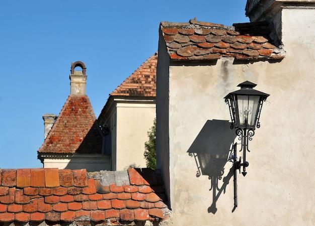 Stara średniowieczna architektura miasta, piękne fasady, malownicze dachy. stara latarnia, wisząca na ścianie w słońcu, rzucająca na nią swój cień.
