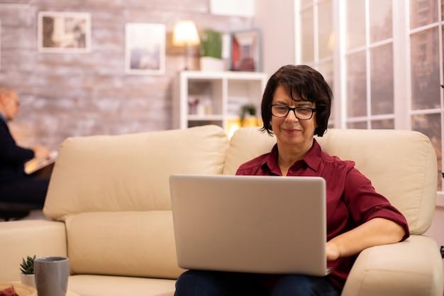 Stara starsza kobieta na kanapie pracuje na nowoczesnym laptopie w swoim przytulnym salonie. jej mąż jest w tle