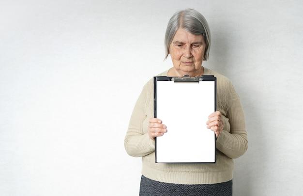 Stara starsza kobieta z pustym białym papierem