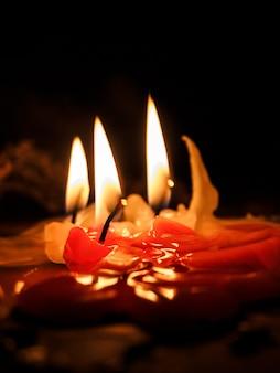 Stara świeca spłynęła po stole. płomienie świec palą się w ciemności.
