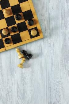 Stara szachownica przycięta z czarno-białymi pionkami na szarej powierzchni drewnianej