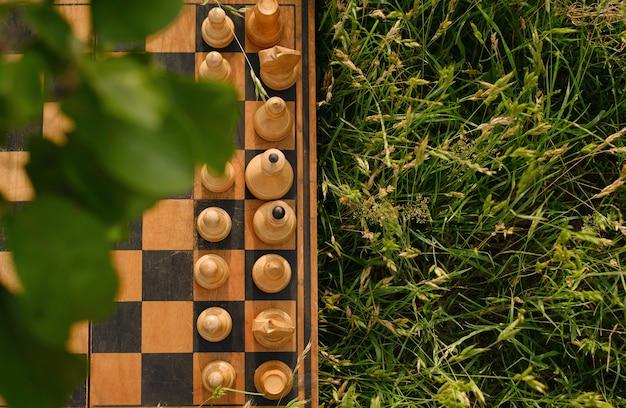 Stara szachownica z figurami umieszczonymi na trawie na starcie