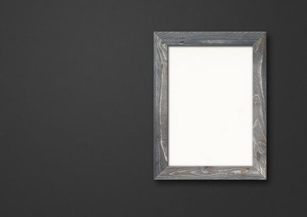 Stara szara rustykalna drewniana ramka na zdjęcia wisząca na czarnej ścianie.