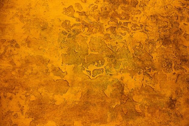 Stara teksturowana kamienna ściana jest pomalowana pomarańczowo-brązową farbą. nierówne zabarwienie, zadrapania, tekstura na pustej ścianie