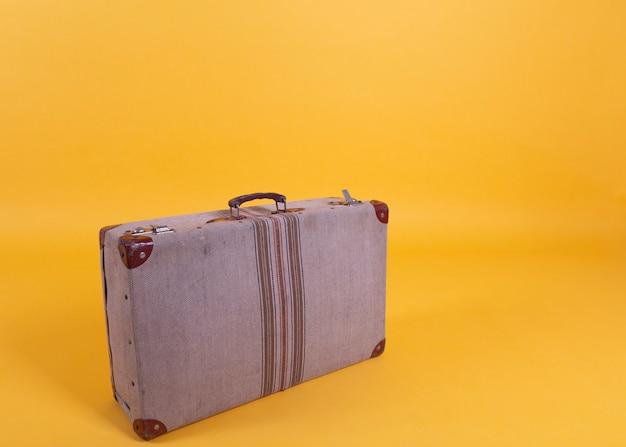 Stara walizka na żółtym tle, podróży pojęcie