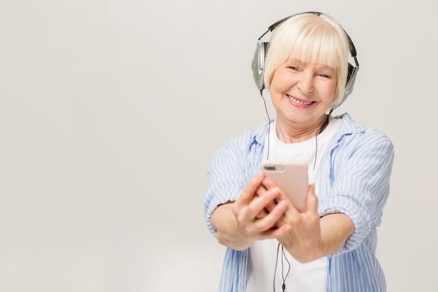 Stara wesoła kobieta ze słuchawkami do słuchania muzyki w telefonie na białym tle. w wieku tańcząca uśmiechnięta dama.