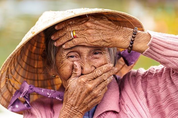 Stara wietnamska kobieta z fiołkową kurtką