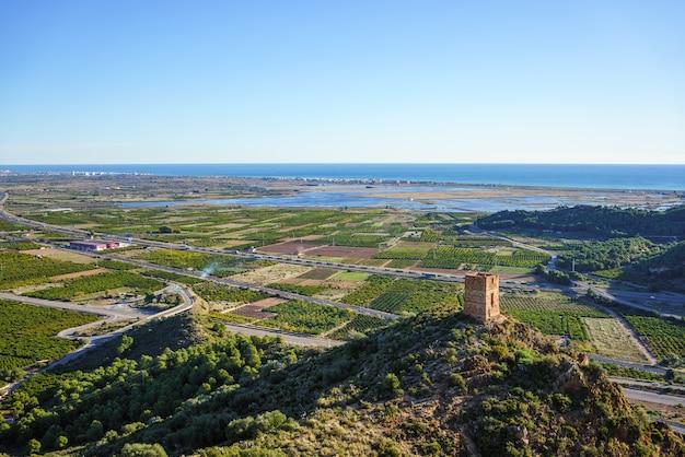 """Stara wieża strażnicza zwana """"l'ageleta"""", pola drzew pomarańczowych, mokradła i morze śródziemne."""