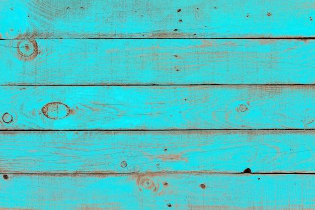 Stara wyblakła drewniana deska pomalowana w kolorze turkusowo-niebieskim.
