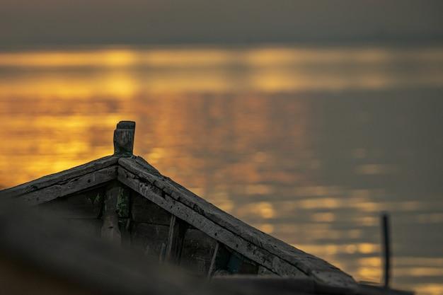 Stara wyblakła łódź do łowienia na wodzie o zachodzie słońca