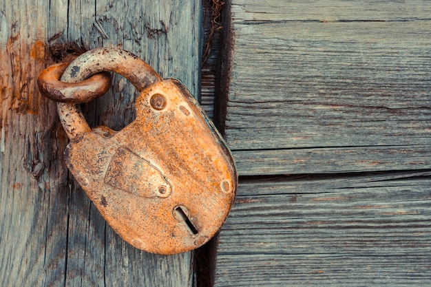 Stara zardzewiała kłódka w metalowej pętli